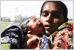Shuki Folia holds her baby who was born in the Catholic church in which she sheltered from the cyclone. The baby is named Bonna which mean 'flood'. Chandpai, Mongla, Bagerhat   ⓒ Kiron/UNICEF
